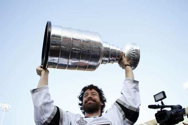 LA Kings player Justin Williams raises the Stanley Cup into the air before the baseball game between the Los Angeles Dodgers and Los Angeles Angels.