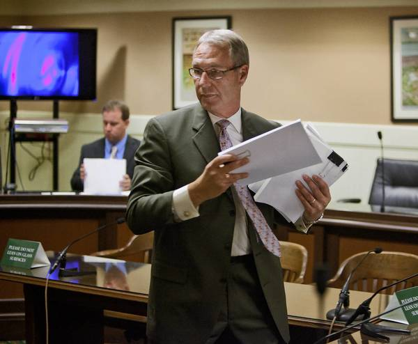 Joe Lang, representing Citizens For Fire Safety Institute, hands out material to legislators Tuesday during a committee hearing in California on flame retardant chemicals in furniture.