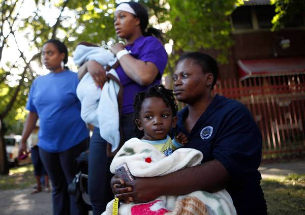 Henrietta Ofili, 41, and her 2-year-old son Samuel sit with displaced residents Tuesday morning as firefighters battle an extra-alarm fire in their apartment building, in the 700 block of East 82nd Street.