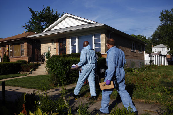 Police investigators work the scene in the 9000 block of South Dobson Avenue on Wednesday. Aletha McGee, 62, was found shot multiple times.