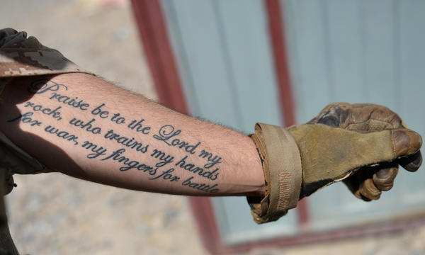 A US Marine from Kilo Company of the 3rd Battalion 8th Marines Regiment shows his tattoo during a patrol in Garmser, Helmand Province, Afghanistan.