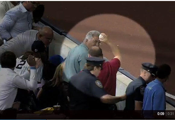 A fan holds up the ball that DeWayne Wise caught, according to umpire Mike DiMuro.