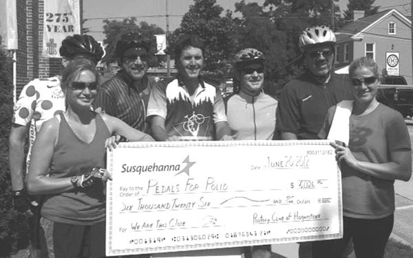 Hagerstown Rotary Club  riders presenting a $6,000 polio campaign check, from left, are Tara Horst, event Chairman Mike Johnston (partially blocked), Alan Levin, Derek Hamilton, Club Vice President Chris Motz, Club President  David Hanlin and Andrea Taylor.