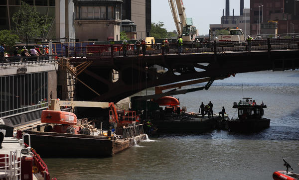 Emergency crews monitor a construction barge that is taking on water and listing this afternoon in the Chicago River in the West Loop Gate neighborhood.