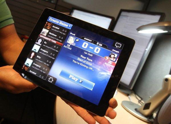 An iPad shows the social media version of Madden NFL as Daryl Holt, Chief Operating Officer and Vice President of EA Sports, talks about the future of gaming platforms --including console, social media and mobile-- during a tour of their Maitland headquarters, Wednesday, June 27, 2012.