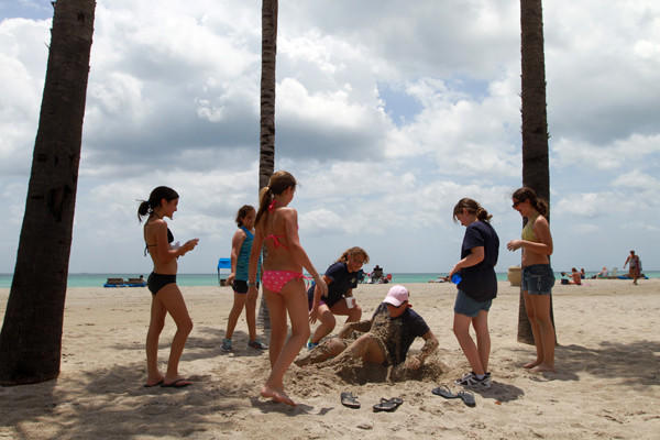 The water at Minnesota Street on Hollywood Beach is tested for pollution twice a month. In 2011, out of 46 total samples 4% exceed state standards and there have been no closing or advisory days. Pictured David Posnack Jewish Community Center Camp Kadima counselor Krystle (cq) Heindman, 23, of Hollywood, sits up after being burried in the sand by her summer campers on Hollywood Beach at Minnesota Street on Wednesday, June 27, 2012. The group was participating in a scavenger hunt and got 1,000 points for getting a photo of Heindman burried in the sand.