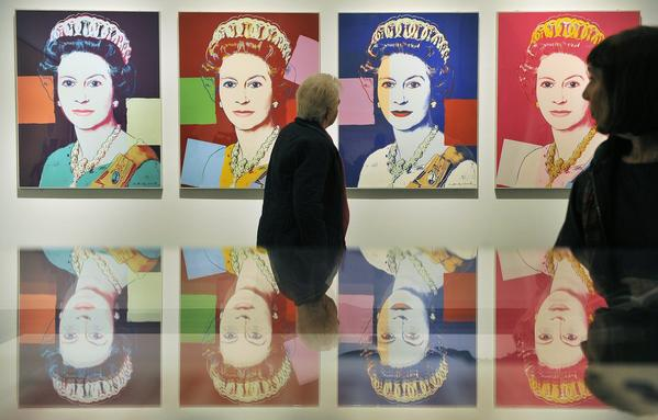 "A museum visitor walks past an Andy Warhol portrait of Queen Elizabeth II in the National Portrait Gallery's exhibition ""The Queen: Art & Image."""