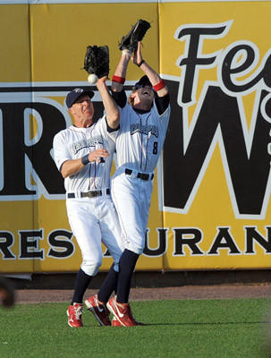 Lehigh Valley IronPigs' left fielder Pete Orr (11) left, and center fielder Kyle Hudson (8) right, collide as they try to catch a fly ball during their game with the Rochester Red Wings at Coca-Cola Park in Allentown Wednesday night.