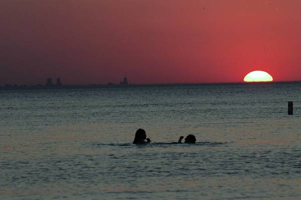 The Chicago skyline and swimmers are lit by the setting sun off Porter, Ind.
