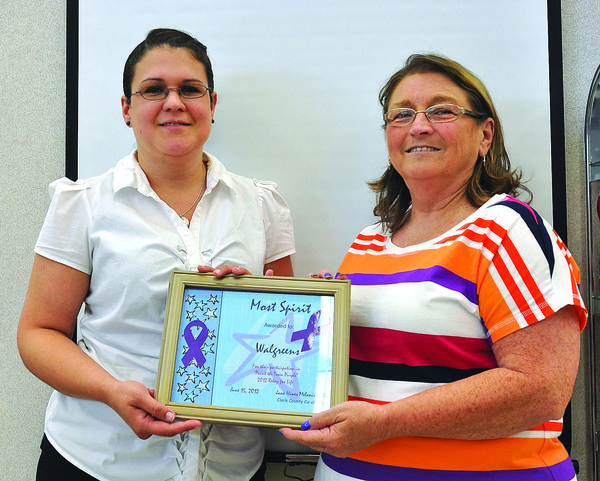 "Jane Hines, right, Clark County Relay for Life Committee co-chairman, presents the ""Most Spirit Award"" to Paige Moreland, manager of the Winchester Walgreens. The store was honored for its participation in the Paint the Town Purple contest to bring awareness to the Relay."