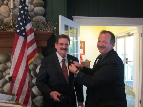 Jim Wibby (right) pins the new president's pin on incoming Rotary Club of Petoskey president Terry Newton.