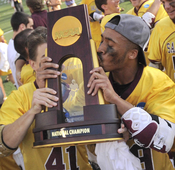 Salisbury's Lantz Carter, left, kisses the NCAA championship trophy while teammate Jeff McGuire keeps a firm grasp on the prize after the Sea Gulls' 14-10 win over SUNY Cortland in the DIII lacrosse championship game.