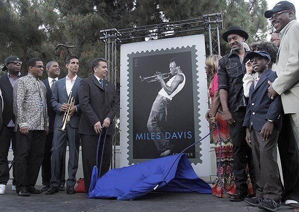 The unveiling of the Miles Davis stamp by Eduardo H. Ruiz Jr., left, L.A. District manager of the USPS, and Miles Davis' daughter Cheryl Davis, right, and musicians and members and friends of the Davis family during the U.S. Postal Service dedication of the Miles Davis stamp before the concert.