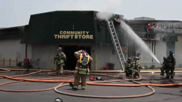 Firefighters shoot water at the roof of the Community Thrift Store in East Dundee.