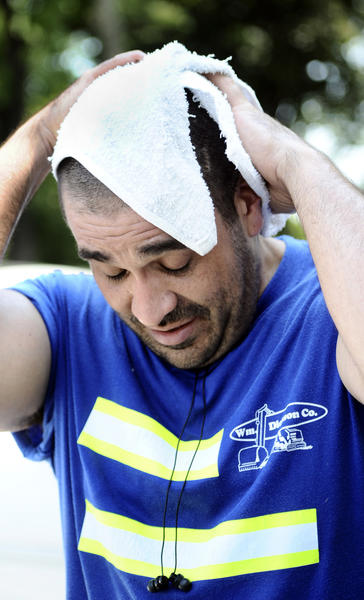 Mike Curran wipes the sweat from his head Thursday during a break from mowing work in Hagerstown.