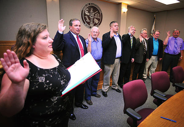 Martinsburg City Recorder Gena Long swears in the new Martinsburg City Council Thursday night. The council members are, from left, Kevin Knowles, Donald Anderson, Jason Baker, Roger Lewis, Max Parkinson, Gregg Wachtel, and Dennis Etherington.