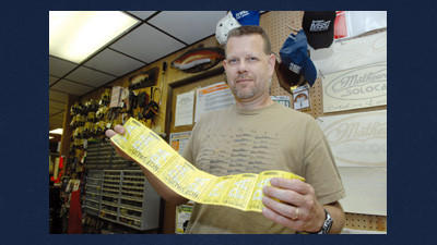 Rich Stoner, owner of S&S Sport Shop in Rockwood, holds a strip of 2012-13 licenses for hunting and trapping seasons.