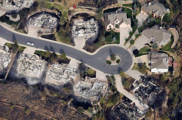Several houses at the end of a cul de sac survived but many others were in ruins after a fire raced through the Mountain Shadows subdivision of Colorado Springs, Colo.