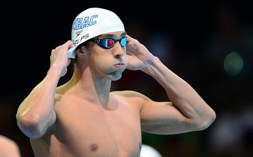 Before finishing in first place in the 200M butterfly final at the U.S. Olympic trials in Omaha on June 29, 2012, Michael Phelps adjusts his swimming cap.