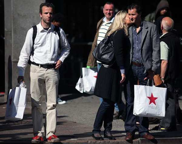 People hold their purchases outside a Macy's in New York. Americans were more cautious about spending in May while their income increased only slightly, indicating the faltering job market has stoked fears about the economy's health.