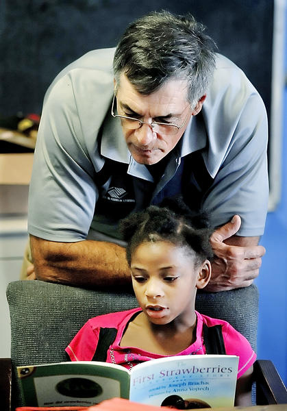 Jim Deaner, executive director of Boys & Girls Club of Washington Co. listens to Zoey Lomax read a book that was in a literacy kit delivered to the club by United Way staff Friday.