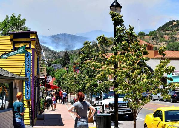 Residents watch as smoke billows in the hills west of Manitou Springs, where hotels sit near-empty. Businesses simply cannot let the Fourth of July holiday pass without cashing in, residents say.