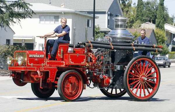 Burbank Fire engineers Terry Mencuri and Kevin Deagon ride a 1915 Christie Front Drive Tractor pulling a 1906 Christie Steam Pumper onto Thornton Avenue in Burbank at Burbank Fire Station 13. The trucks, acquired from Warner Bros. and originally used by the Los Angeles Fire Department, were restored by firemen at the station interested in preserving the department's history. The mechanical history is now being passed on to the newer fireman.