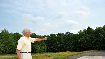 R. Dean Hillegas stands at the dead end stretch of Route 219 in Somerset Township. He was part of a group that advocated the highway's completion decades ago.