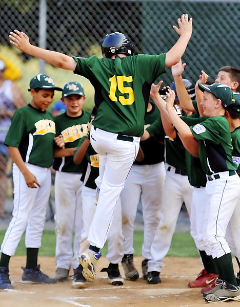 West End's Joseph Ringus (15) leaps into home plate as teammates greet him after his two-run home run in the first inning against Clear Spring in the Maryland District 1 10-11 Tournament championship game Friday night.