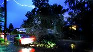 Lightning lights the sky as a motorist navigates around a downed tree on Regester Avenue in Towson. A severe thunderstorm passed through the region late Friday leaving many without power.