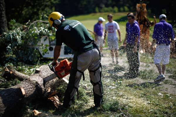 A chainsaw is used to cut a tree that fell onto the 14th fairway during an overnight storm in the Washington area.