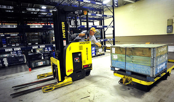Material handler George Lynch scans a container of truck engine parts Thursday after pulling them from an aisle inside the Volvo truck plant. The truck manufacturer reorganized their space to accomodate an on-site parts inventory.