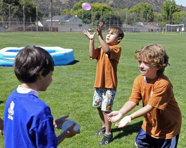 Campers Aram Abramian, left, Timmy O'Brien, center, and Francesco Gambino, right, participate in an olympic-themed balloon toss event during Camp Runamuk at the Community Center of La Canada on Friday.
