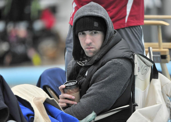 Olympic gold medal swimmer Michael Phelps sits bundled up poolside in Naval Academy's Lejeune Hall.
