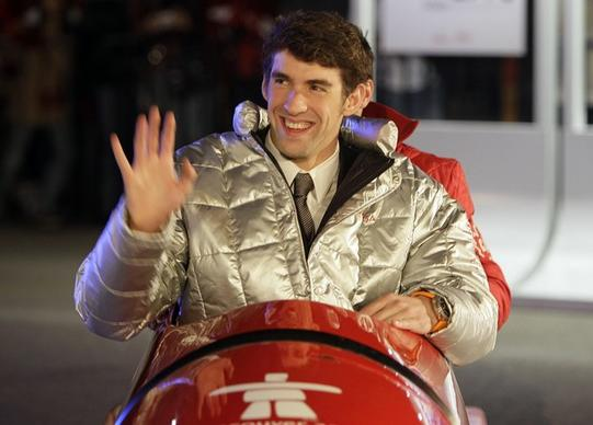 Olympic swimming gold medalist Michael Phelps sits in a bobsled while making an appearance in downtown Vancouver during the 2010 Winter Olympics.