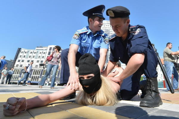 Policemen arrest activists of Ukrainian women's movement FEMEN protesting in front of the Olympic stadium in Kiev against the UEFA and against the visit of Belarus President Alexander Lukashenko to attend final match of the EURO 2012 opposing Italy to Spain on July 1, 2012. A number of Ukrainian human rights organisations have called on European leaders to pressure President Viktor Yanukovych to withdraw Lukashenko's invitation and boycott the final.