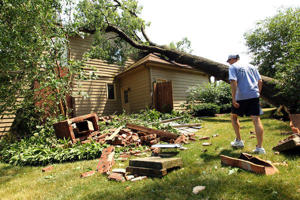 Chad Pechman walks through his yard after a neighbor's tree fell on the roof of his home during a storm in West Chicago on Sunday. The Pechman family just moved into this house on Rosewood Drive yesterday.