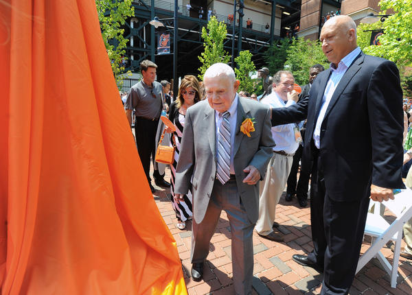 Former Orioles manager Earl Weaver, center, walks pass Cal Ripken Jr., right, and the covered statue before the unveiling ceremony.