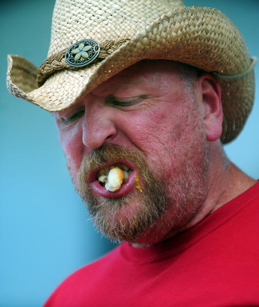 Rich Grey of Easton, Penn., eats during the contest at the Hot Dog Fest at Young Park in Hollywood, Sunday, July 1, 2012. Grey took a break from his honeymoon to participate.