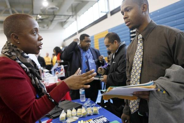 Deborah Reid, of Edward Hines, Jr. VA Hospital, gives information on finding government jobs to veteran Jarriel Walker of Chicago during a job fair in 2011 at Richard J. Daley College.