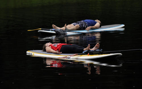 Maggie Hart of Simsbury and Shawn Cole lie peacefully on their paddle boards to end the yoga paddle boarding session on the Farmington River.