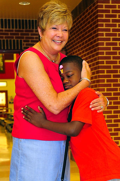 Ruth Ann Monroe Elementary School principal gets a morning hug Wednesday morning from second-grade student Kyandre Jones. Ellen Hayes is retiring at the end of the school. Keyandre came to school wearing an ice cream sticker on his forehead.