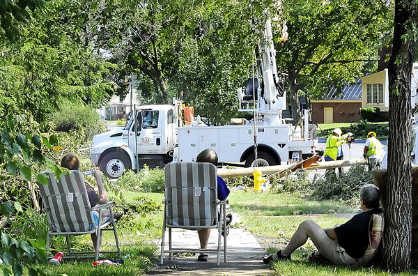 Residents living near the intersection of Race St. and N. Alabama Ave. in Martinsburg watch as a utility crew from Sumter, South Carolina, put up a new power line pole. Some of the residents have been without power since the storm.