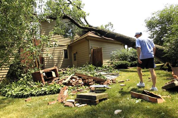Chad Pechman surveys his yard after a neighbor's tree fell through the roof of his home during a storm in West Chicago on Sunday. The family moved into the house Saturday.