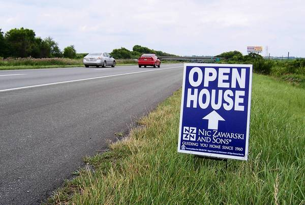Signs such as this one directing motorists to 'open house' home-sale events are posted along highways in the region, much like campaign signs during election season.