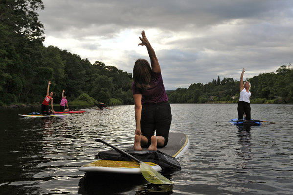 Leslie Gordon, an instructor at the Yoga Center of Collinsville, helps lead a new class that incorporates yoga and paddle boards.