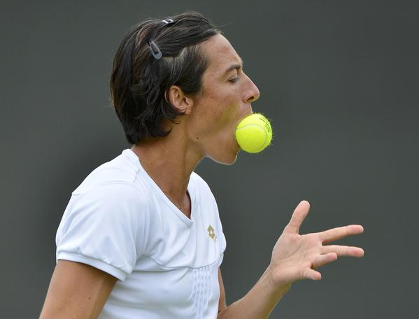 Francesca Schiavone of Italy holds a ball in her mouth during her women's singles tennis match against Petra Kvitova of the Czech Republic at the Wimbledon tennis championships in London.