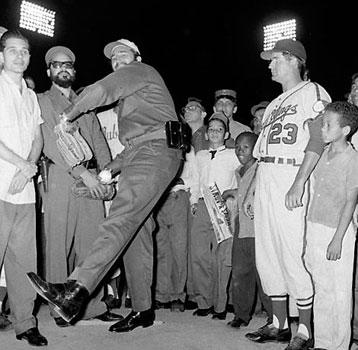 Cuban leader Fidel Castro, a college baseball pitcher turned revolutionary, rears back to toss the traditional first ball at ceremonies preceding inaugural of International League Season in Havana in this April 20, 1960 file photo. At right looking on is Rochester Red Wings manager Clyde King whose team met the Havana Sugar Kings in the season opener.