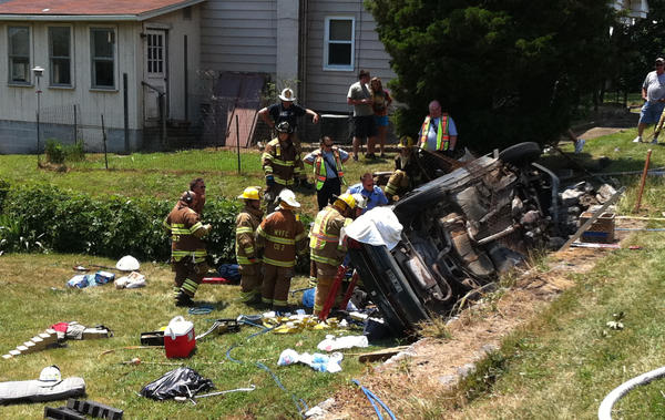 Firefighters work to extricate the driver from a vehicle that went off the 15500 block National Pike (U.S. 40) Monday afternoon and rolled over into a nearby yard.