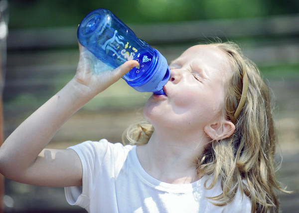 Amalie Nohe-Moren, 6, of Baltimore, a camper of the Nature Nuts Summer Nature Camp at Irvine Nature Center, takes a water break to cool off after playing outdoors.